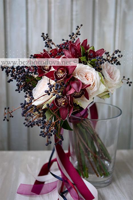 Букет из орхидей цвета марсала, кремовых пионовидных роз и синих ягод