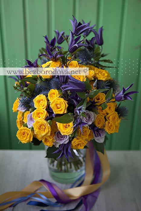 Желтый букет в подарок из кустовых роз, с фиолетовыми клематисами, синим эрингиумом и сиреневой розой