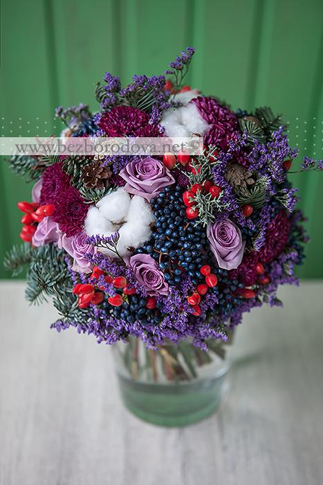 Зимний свадебный букет с хлопком, шишками, ветками ели, синими и красными ягодами, сиреневыми розами и винной хризантемой