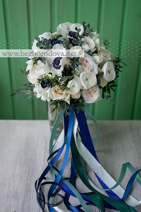 Белый свадебный букет из ранункулюсов, анемонов, пионовидных роз, фрезий и синих ягод вибурнума с мятной зеленью эвкавлипта