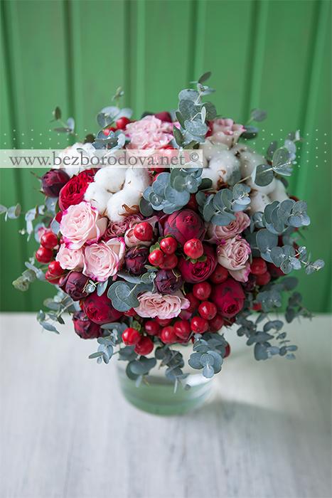 Красный свадебный букет из пионовидных роз с ягодами гиперикума, хлопком, мятным эвкалиптом и розовыми кустовыми розами