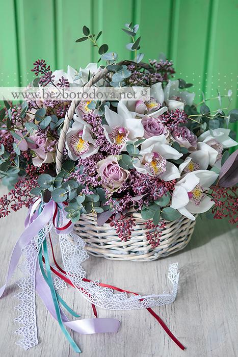 Подарочная корзина из белых орхидей цимбидиуми сиреневых роз с зеленью эвкалипта