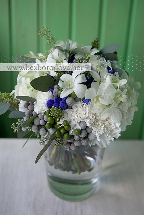 Белый свадебный букет из орхидей дендробиум, гвоздики, синей гентианы с серой зеленью эвкалипта и зелеными ягодами гиперикума