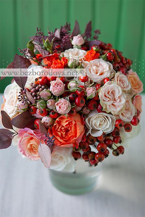 Осенний букет невесты с ягодами шиповника, оранжевыми пионовидными розами и коричневым эвкалиптом