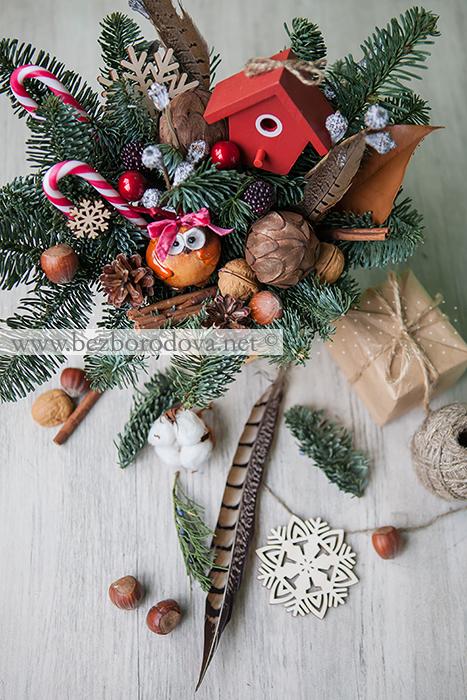 Новогодняя композиция из голубой ели с совой, елочными игрушками, шишками, орехами и перьями