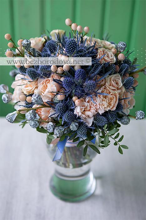 Кремовый свадебный букет из роз и гвоздик с ягодами гиперикума, синими эрингиумами и серыми бутонами эвкалипта