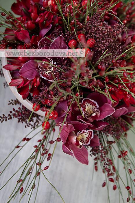 Букет из винных орхидей цимбидиум, красной альстромерии и ягод гиперикума в корзине