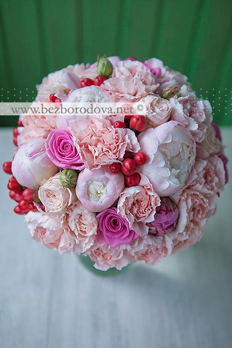 Персиковый свадебный букет из пионовидных роз и пионов с красными ягодами гиперикума