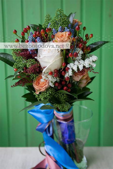 Свадебный букет свободной формы из коричневых роз, ягод гиперикума с голубыми мускари и зеленой скиммией